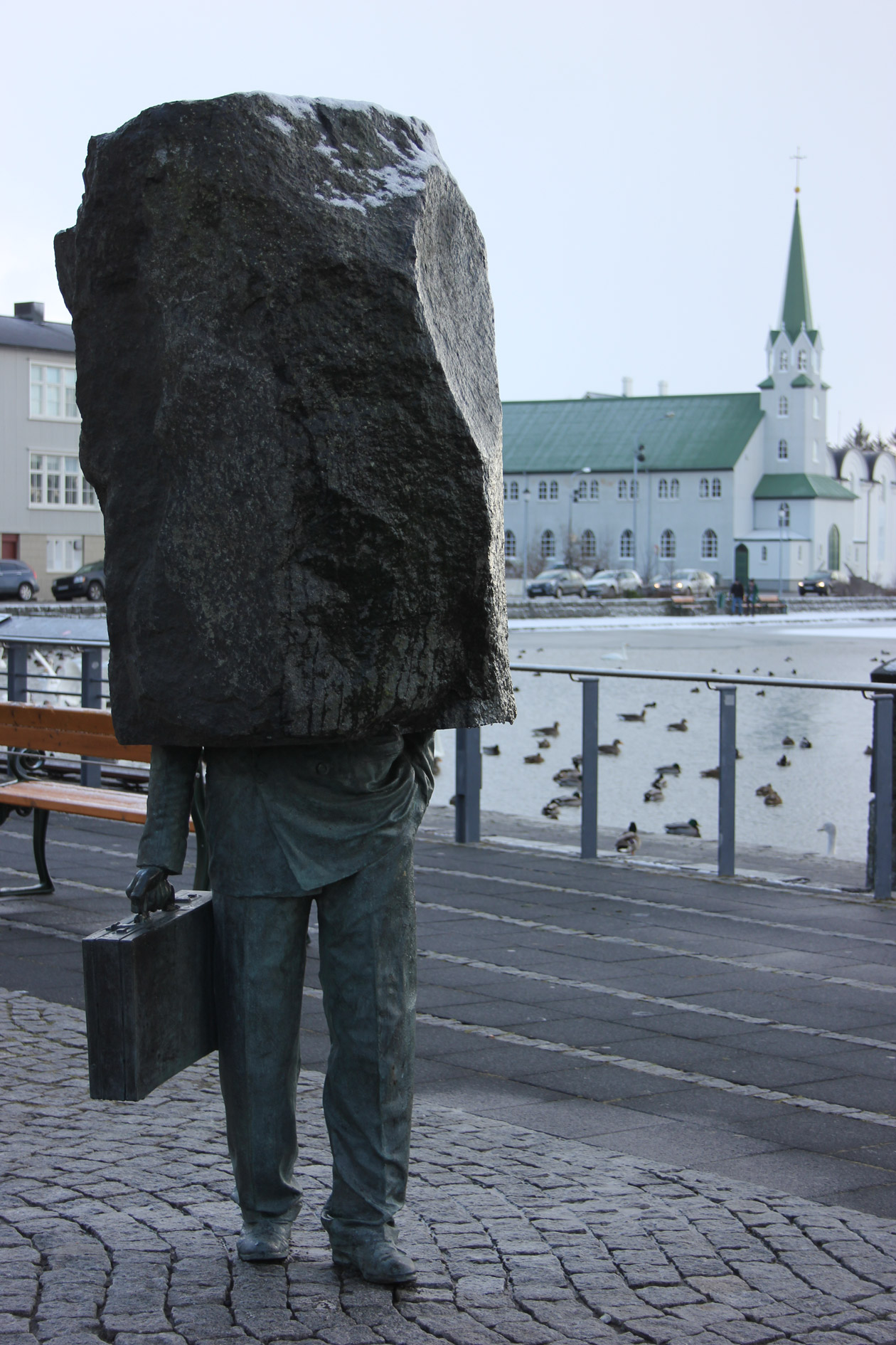 A sculpture beside the Reykjavíkurtjörnin lake with the Free Church in the background