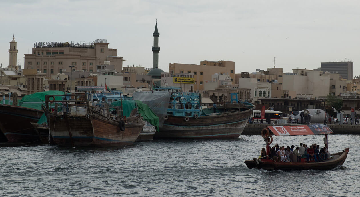 An abra crossing the Dubai Creek in front of dhows