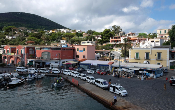 Arriving in Ischia Porto. The dark pink building with the arched windows houses the ticket offices for all services apart from Alilauro.