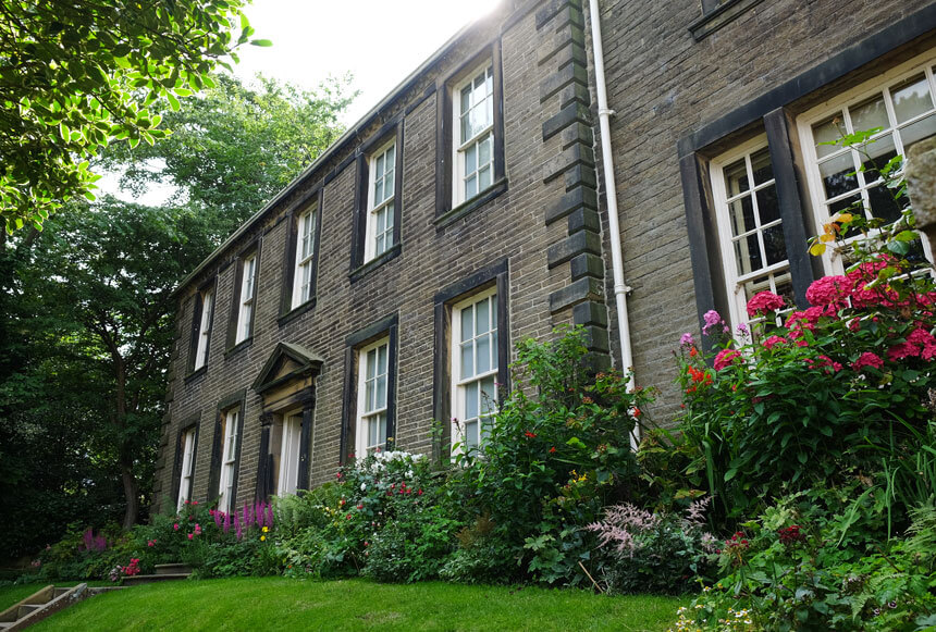 The Brontë Parsonage Museum in Haworth celebrates the life of Charlotte, Emily and Anne Brontë. A stone house with large windows sits in a beautiful cottage garden with lots of flowers.