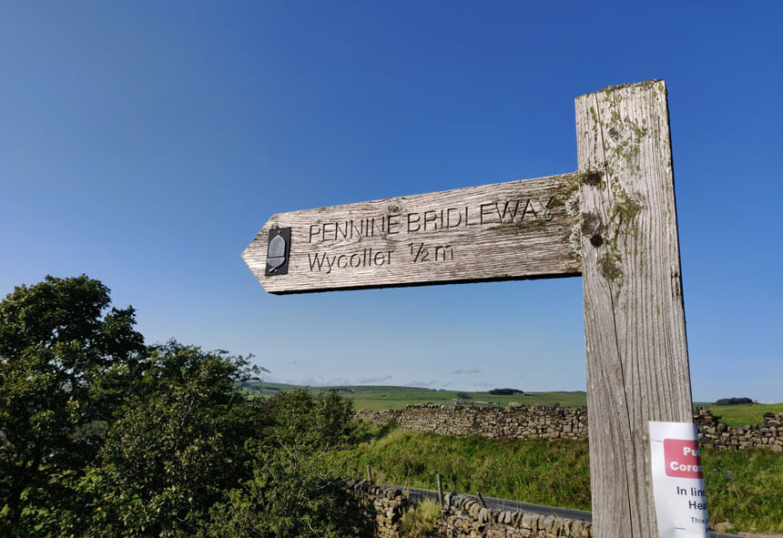 The Pennine Bridleway runs through Wycoller. A wooden sign reading Pennine Bridleway and pointing to Wycoller half a mile away.