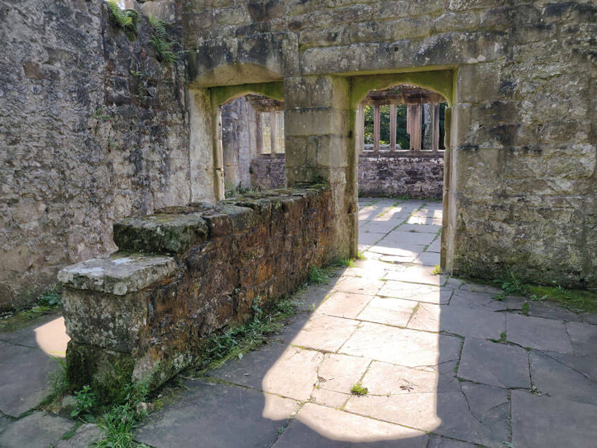 Wycoller is one of England's most haunted villages. Two arched doorways in a ruined stone house. The sun is shining through the doorways, making a pattern on the stone flagged floor.