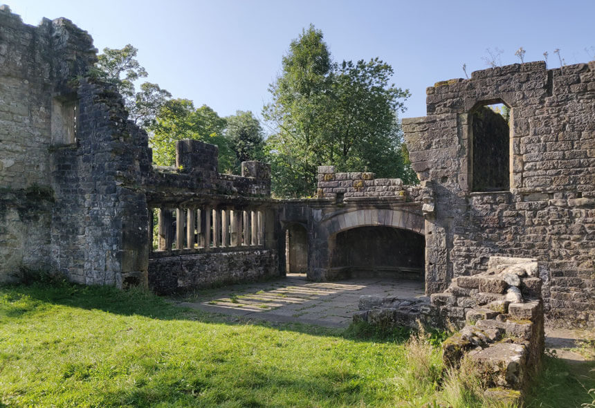 It's free to wander around the ruins of Wycoller Hall. A large room has a partially flagged floor with mullioned windows and an enormous fireplace.
