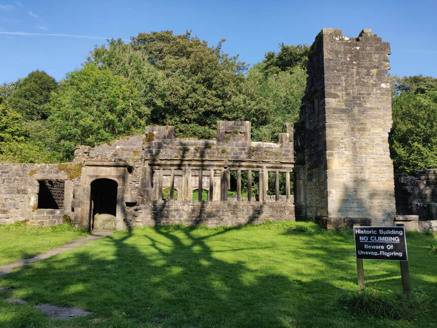 The ruins of Wycoller Hall, which inspired Charlotte Brontë. A ruined stone house with mullioned windows and a tower sits on a green grass lawn.