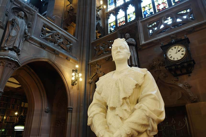 A white marble statue of Enriqueta Rylands in the reading room of the library she built. There are stone arches, statues, books and a stained glass window behind her.