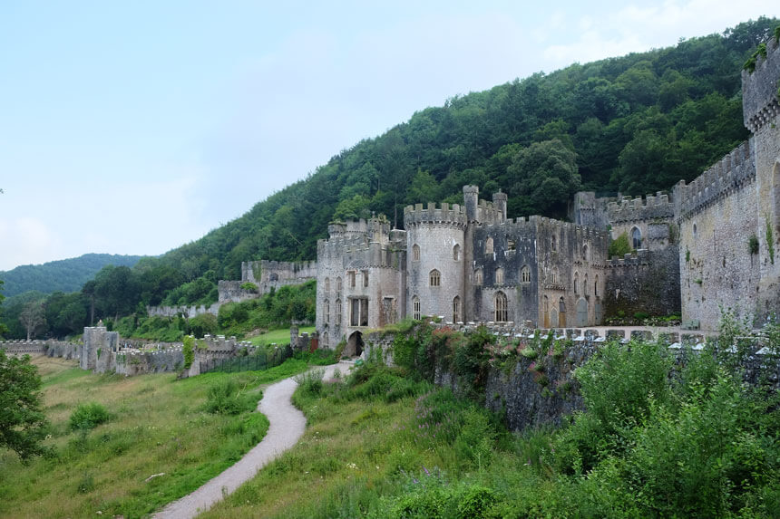 Gwrych Castle in Abergele, North Wales. A large, long castle with towers and castellated walls is set into a Welsh hillside.