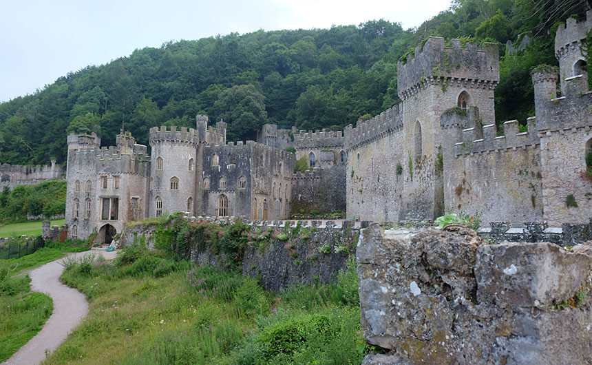 The outside of Gwrych Castle in North Wales. A ruined, roofless but very grand castle in grey stone with gothic towers spreads across a forested Welsh hillside.