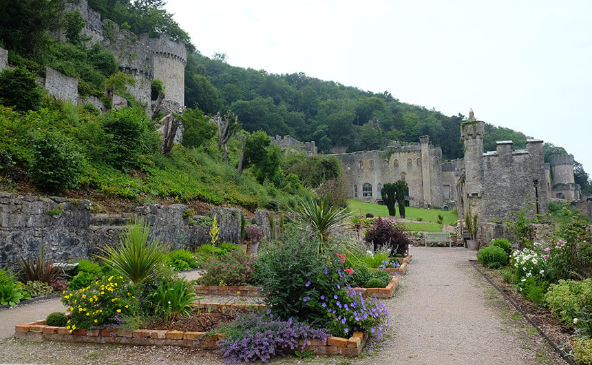 The gardens at Gwrych Castle in North Wales. Borders full of plants with yellow, purple, white and pink flowers and a green grass lawn are laid out in front of a gothic stone castle.