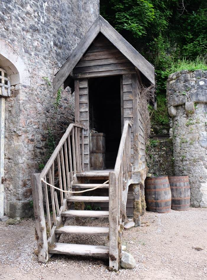 A narrow wooden shed-like building is up some wooden stairs in a castle courtyard. There are stone walls, a small stone tower and some barrels that look like props in the background.