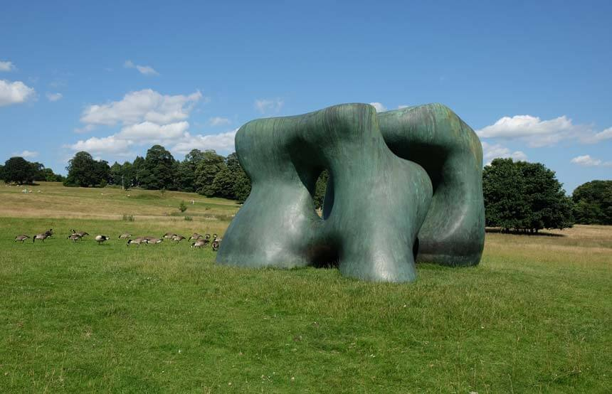 Henry Moore's bronze Two Large Forms. Two greeny-coloured, large bronze sculptures are set in a rolling landscape at the Yorkshire Sculpture Park. A flock of Canada geese are enjoying eating the grass next to the sculpture.