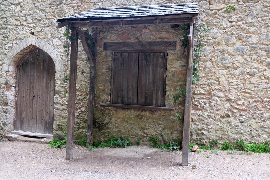 The Ye Olde Shoppe from I'm A Celeb at Grywch Castle. A wooden hatch is in a stone wall with a rickety roof over the top.