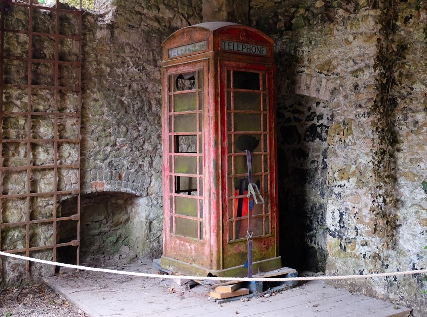 A rusty old red telephone box that was used in I'm A Celebrity... Get Me Out Of Here! is in the corner of an old stone outbuilding.