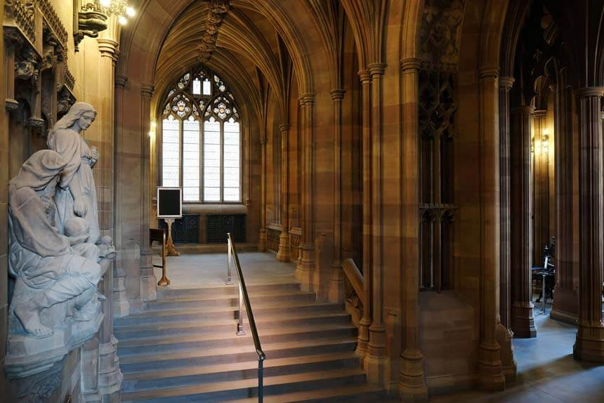 The main entrance hall at the John Rylands library has tall stone columns and a wide stone staircase. It has the air of a cathedral or Hogwarts