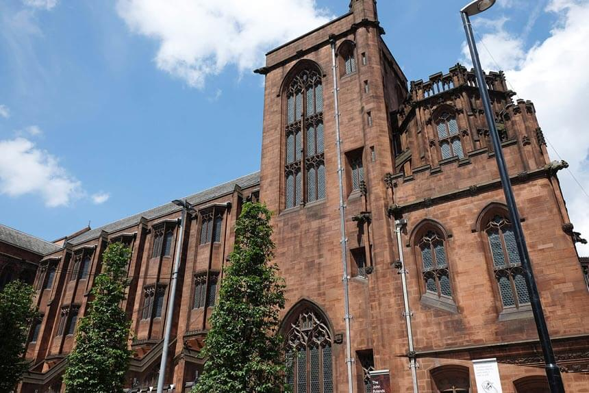An exterior photo of the John Rylands Library in Manchester. The library is a Gothic style building with arched windows, made of pink stone.