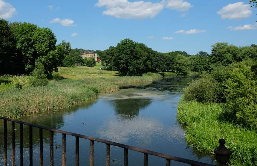 Bretton Hall and its lovely parkland surroundings. There is a lake with reeds in the foreground of the image. Further back is rolling green grass and trees. In the distance there is an old country hall in golden stone.