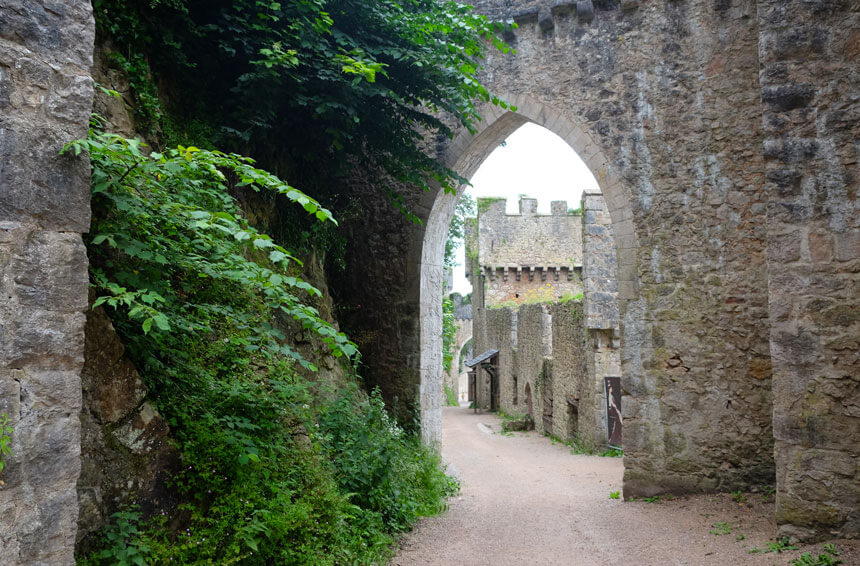 Looking towards the main gate at Gwrych Castle. A narrow lane leads downhill past old stone buildings, a square tower and a circular tower. The walls are rather overgrown and the buildings are in disrepair.