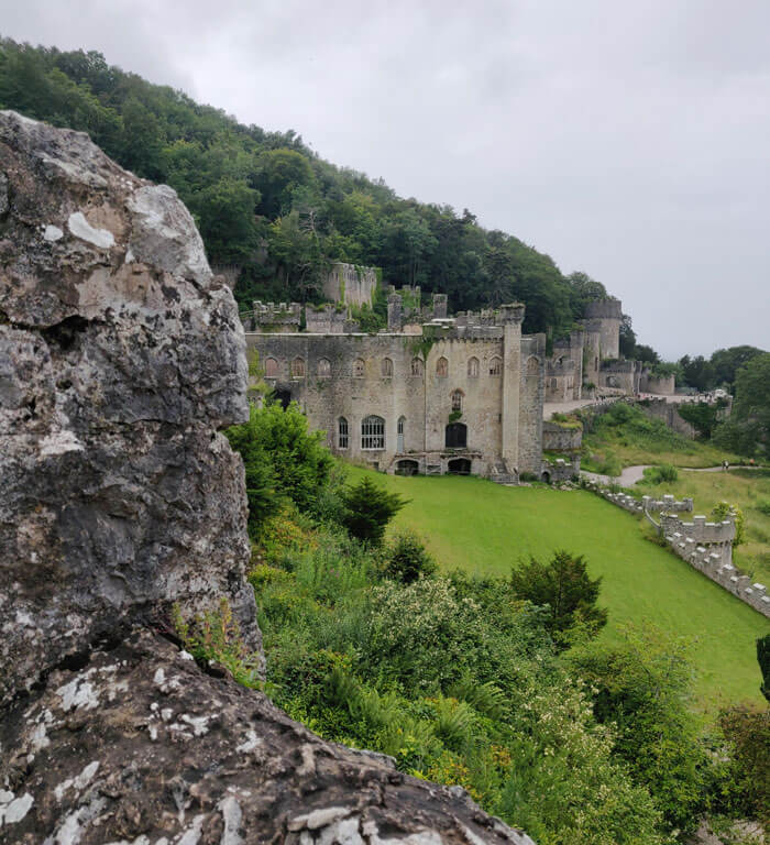 The scene from Nant-y-Bella Tower at Gwrych Castle. A once-grand but ruined Gothic style house with a large grassy lawn in front and woods behind.