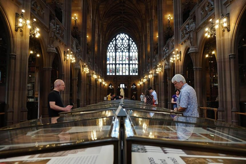 The majestic reading room at the John Rylands Library in Manchester. A large room, with a huge and elaborate stained glass window at one end and lined with stone columns and dim lights. People are looking at displays in glass cases.