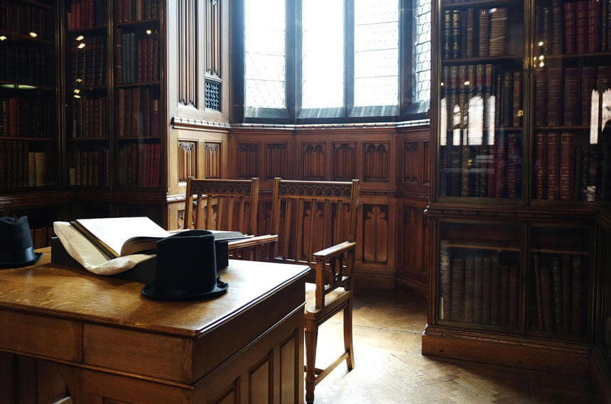 The edges of the John Rylands Library's reading room are lined with wood-panelled study nooks. The nook in the photo has a wooden desk and two wooden chairs. There are bookshelves containing large leather-bound books on either side of the window.
