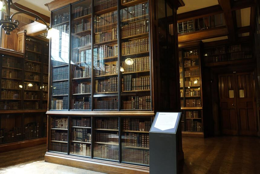 The Spencer Room at the John Rylands Library. Dark wood bookshelves are filled with old, leather-bound books up to the ceiling.