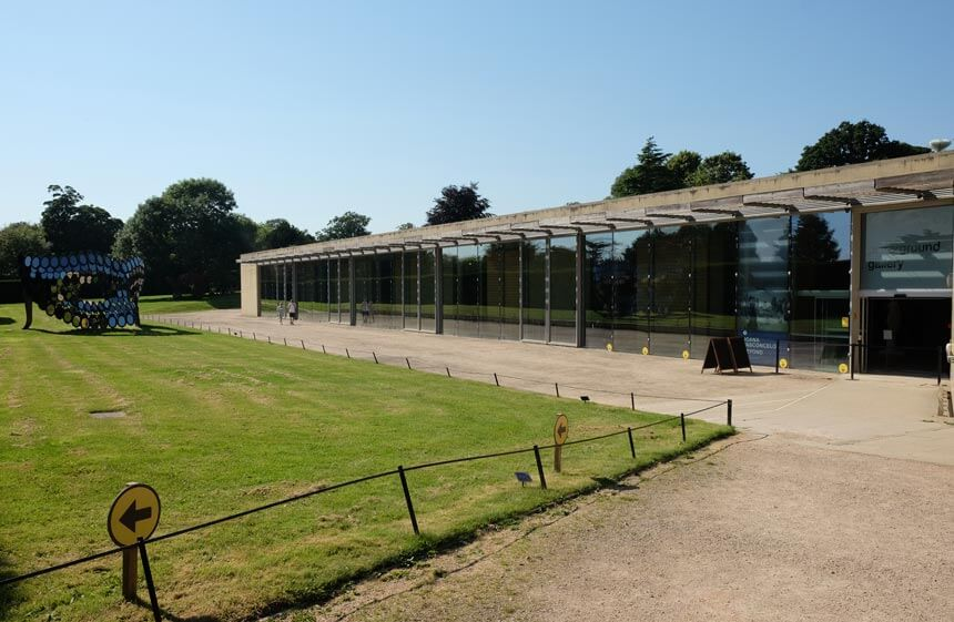 The Underground Gallery at Yorkshire Sculpture Park. A long, glass-fronted modern building with a walkway in front. There is a large sculpture of a mirrored masquerade mask on the grass on the other side of the walkway.