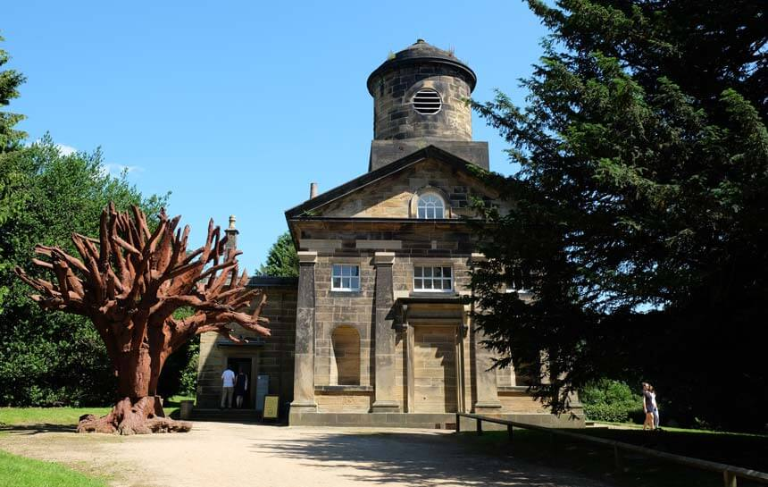The old Bretton Hall chapel with an iron tree sculpture next to it. The chapel is an old stone building in the classical style, with a circular tower topped with a small dome. There are people entering the chapel gallery on the left hand side and some leaving on the right, walking into the graveyard which is grassy and full of trees.