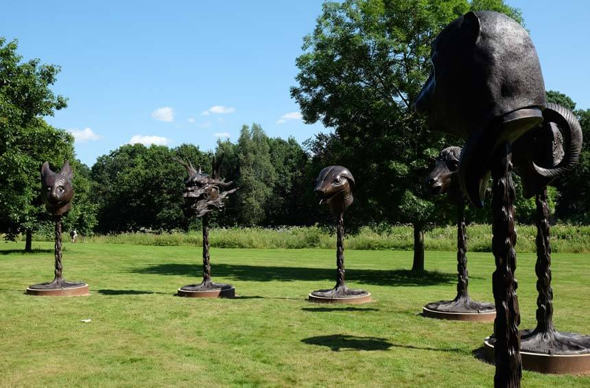 Ai Weiwei'sCircle of Animals/Zodiac Heads. A series of bronze animal heads depicting the Chinese zodiac signs stand on poles in a grassy park. They are set in a circle.