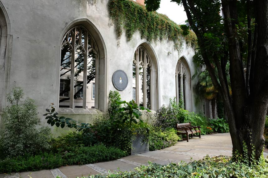 The garden at St Dunstan in the East, an old church which was bombed during the London Blitz. The photo shows the plants, trees and benches inside the church, against a backdrop of the old arched windows.
